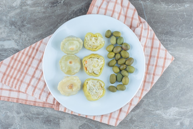Filled green pepper and olive on white plate.