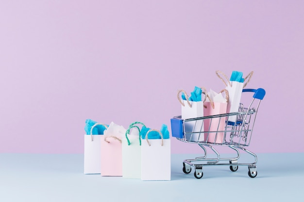 Filled miniature cart with paper shopping bags in front of pink background