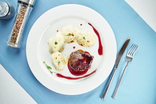 블루 식탁보에 흰색 접시에 베리 소스와 감자 뇨키를 곁들인 필레 미뇽 스테이크 미디엄 레어