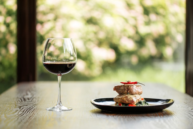 Fillet mignon steaks with sauce glass of red wine