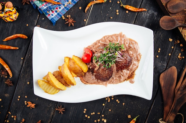 Fillet mignon steaks with sauce and potato wedges