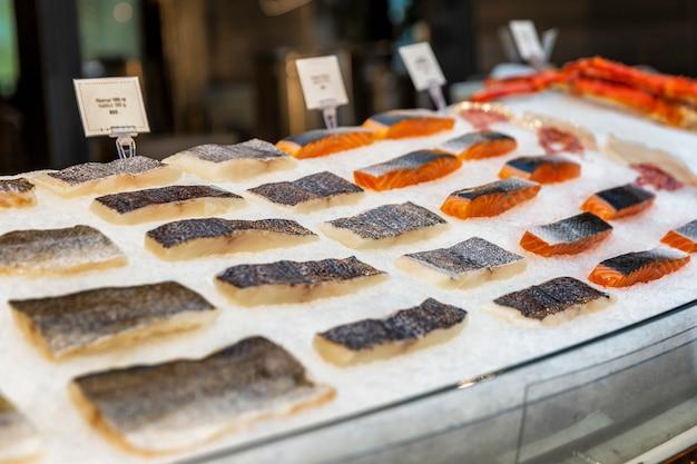 Филе разнообразной свежей рыбы на льду в окне ресторана. свежий улов.