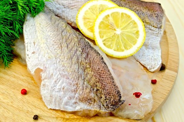 レモンとコショウの実と丸いプレート上のタラの切り身、木製のテーブルの上のディル