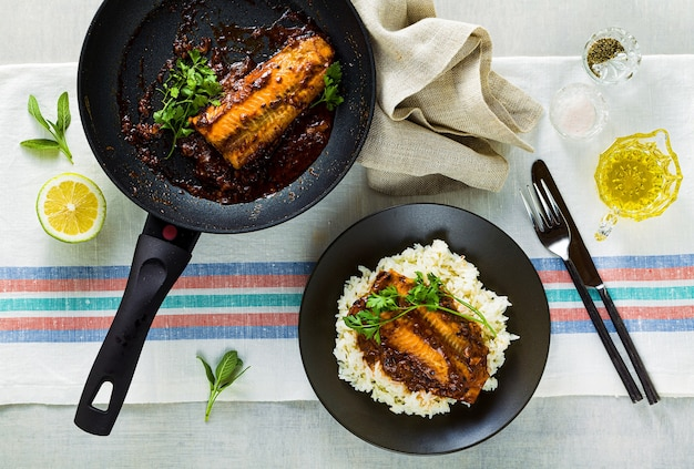 Филе горбуши в томатно-кокосовом соусе на антипригарной сковороде с петрушкой на столе с льняной скатертью. здоровая семейная еда с рисом басмати