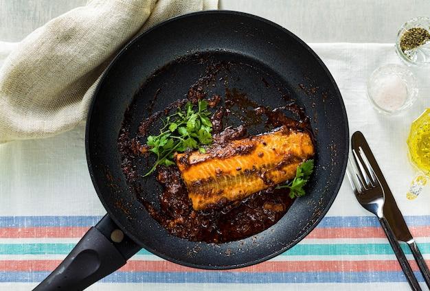 Филе горбуши в томатно-кокосовом соусе на антипригарной сковороде с петрушкой на столе с льняной скатертью. здоровая семейная еда
