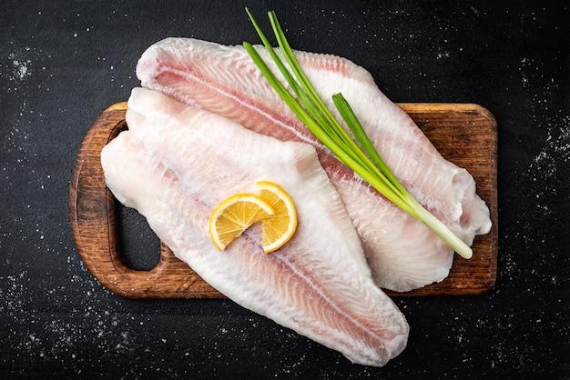 暗い背景のまな板にレモンとネギと生のパンガシウス魚の切り身。上面図。