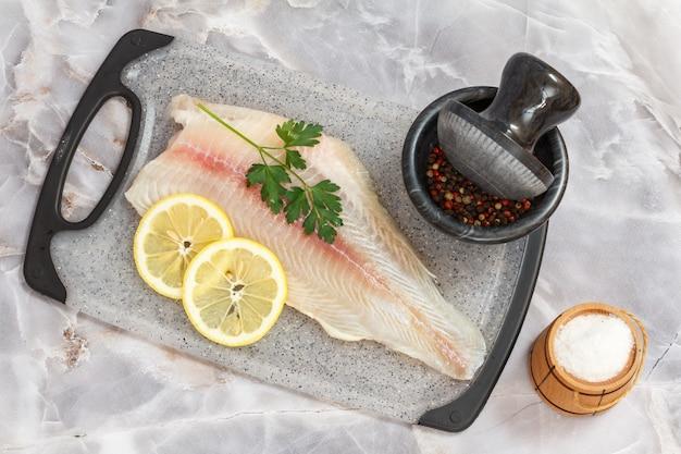 まな板の上にパセリの葉とレモンと生のパンガシウス魚の切り身