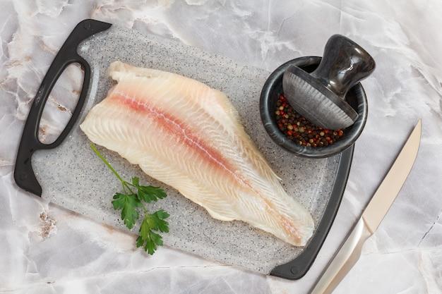 石の台所のテーブルの上に置くまな板の上にパセリの葉とスパイスを添えた生のパンガシウス魚の切り身。上面図。