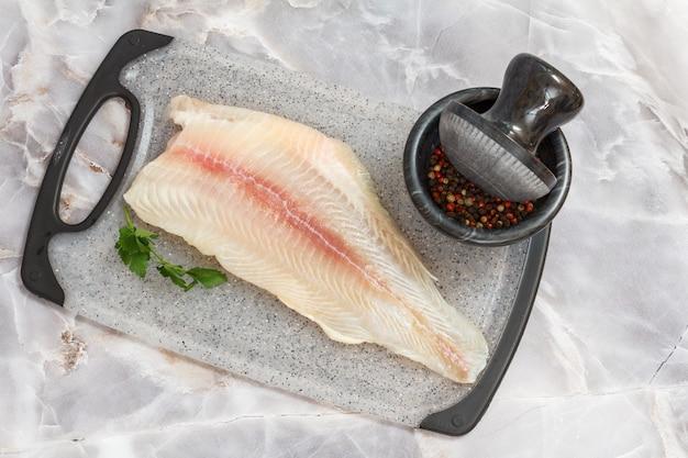 石の台所のテーブルの上に置くまな板の上にパセリの葉とスパイスと生のパンガシウス魚の切り身