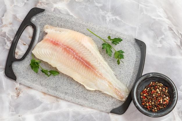 まな板の上にパセリの葉とスパイスと生のパンガシウス魚の切り身