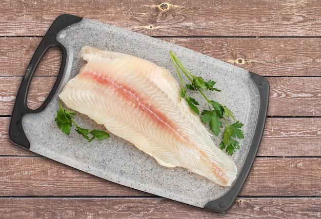 まな板と木の板にパセリの葉を添えた生のパンガシウス魚の切り身。上面図。