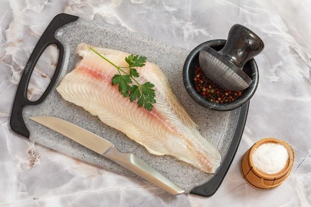 石のキッチンテーブルの上に置くまな板の上にパセリの葉、塩、スパイスを添えた生のパンガシウス魚の切り身。上面図。