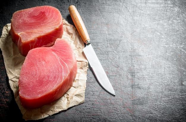 Филе сырого тунца на бумаге ножом. на темном деревенском фоне