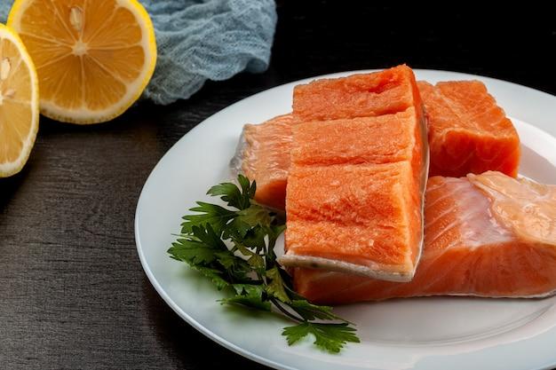 皿の上の赤いマスの魚の切り身。木製の背景にマス