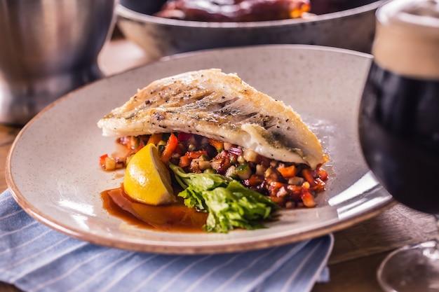 Филе судака с овощами на тарелке в ресторане.