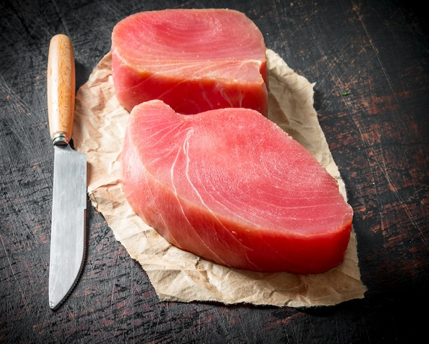 Fillet of raw tuna on the paper with a knife on dark rustic table