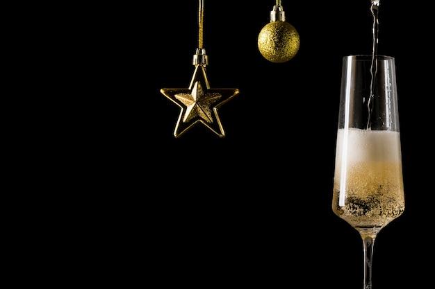 Наполнение бокала шампанского и украшения в виде звезды и шара. популярный алкогольный напиток.