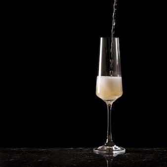 Наполнение бокала шампанским. популярный алкогольный напиток.