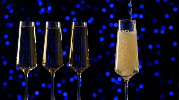 Наполнение бокала игристым вином. популярный алкогольный напиток.
