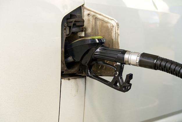 Filling car with diesel. black oil dispenser at gasoline station. refueling old minivan euro3 with diesel en90.