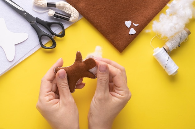 Filling the felt christmas gingerbread man with holofiber. step-by-step manufacturing instructions. step 6.
