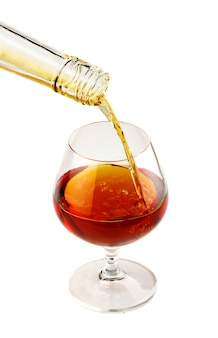Filling a glass of brandy isolated
