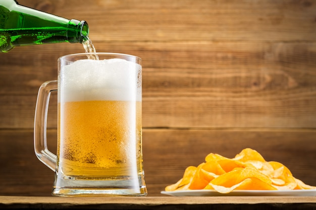 Filling a glass with beer on wooden wall.