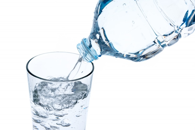 Filling glass with water from plastic bottle