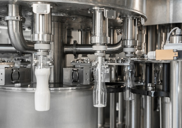 Розлив молока в пластиковые бутылки на заводе. оборудование на молочном заводе
