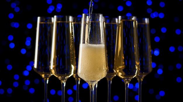 Наполнение одного из пяти бокалов игристым вином на синих огнях боке. популярный алкогольный напиток.
