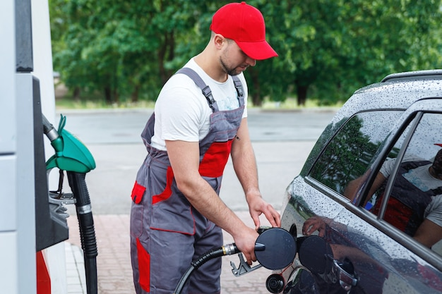손에 연료 노즐을 들고 고객의 자동차 탱크를 채우는 주유소 직원