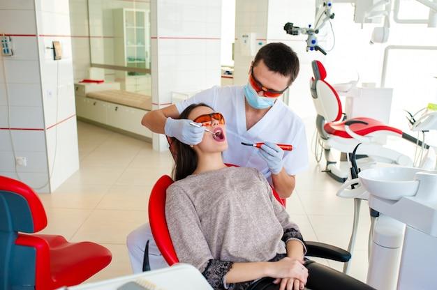 Filling teeth in a girl in dentistry.