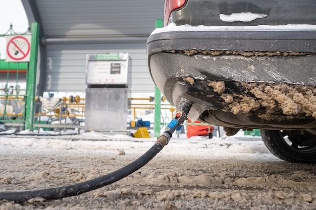 Заправка машины газом снизу от бампера зимой на заправке.