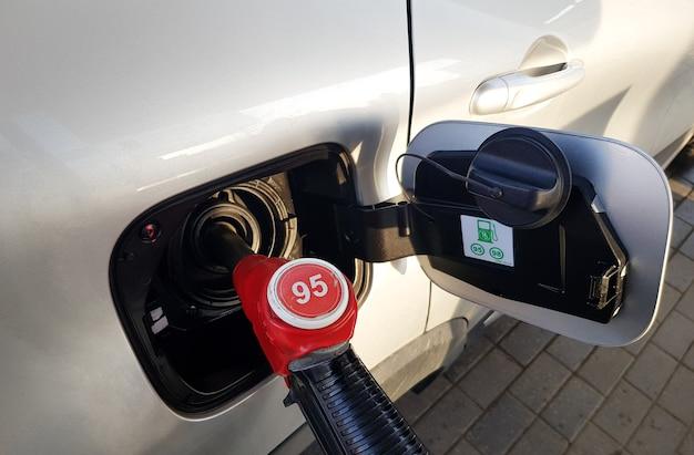 車にガソリンを充填する燃料補給のために赤い銃を車のタンクに挿入します