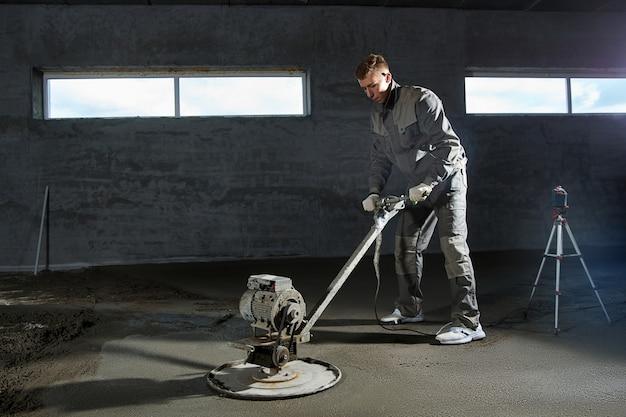 建設作業員が床をコンクリートで埋め、スクリードし、床を平らにします。セメント、工業用コンクリートの混合物で作られた滑らかな床