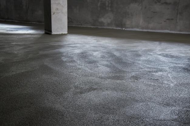 床をコンクリートで満たし、スクリードし、床を平らにします。セメント、工業用コンクリートの混合物で作られた滑らかな床