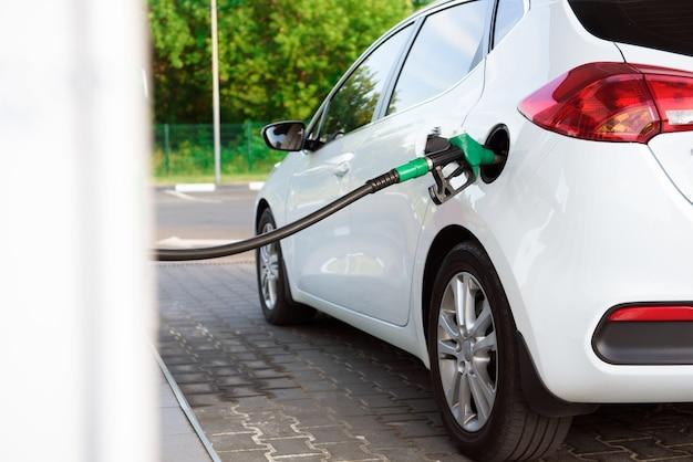 機械に燃料を充填します。車はガソリンスタンドでガソリンでいっぱいです。男は車の保持ノズルにガソリン燃料を充填します。