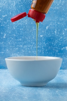 Filling a white bowl with honey.