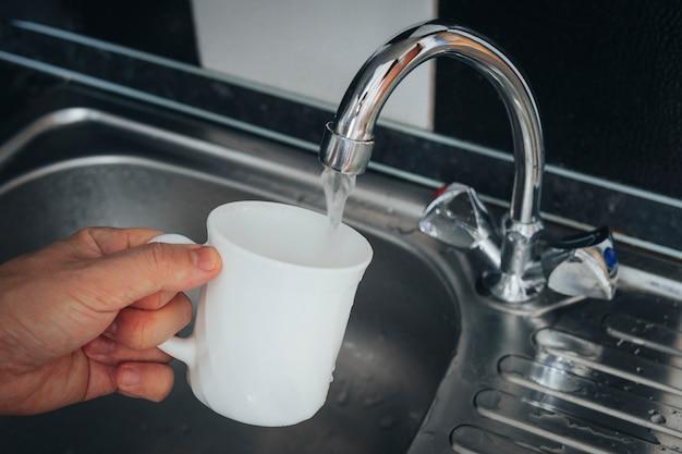 수돗물로 흰색 유리를 채우십시오. 가정 부엌에 있는 현대적인 수도꼭지와 싱크대. 컵에 신선한 음료를 붓는 남자.