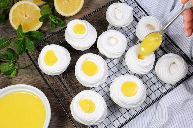 랙에 레몬 커드로 속을 채운 섬세하고 바삭한 미니 디저트 파블로바