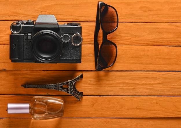 Пленочный фотоаппарат, солнцезащитные очки, флакон духов, сувенирная статуя макета эйфелевой башни на цветной деревянный.