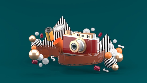 Film camera surrounded by film and colorful balls on a green space