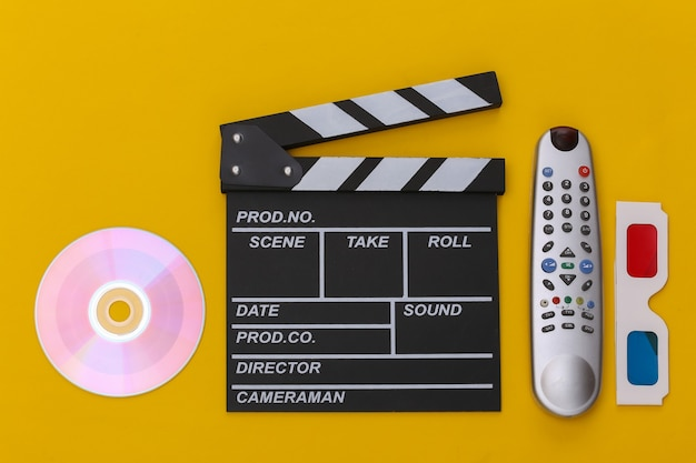 Пленка с хлопушкой, 3d-очки, cd и пульт от телевизора на желтом фоне. вид сверху