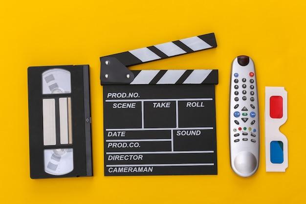 Пленка с хлопушкой, 3d-очки, видеокассета и пульт от телевизора на желтом фоне. вид сверху