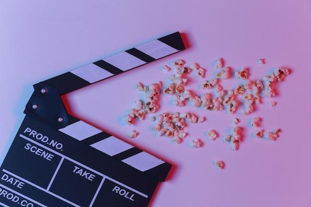 Пленка с хлопушкой и попкорн в красно-синем неоновом градиентном свете. киноиндустрия, развлечения