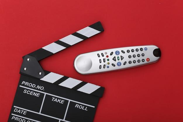 Доска с хлопушкой фильма и пульт от телевизора на красном фоне. киноиндустрия, развлечения. вид сверху