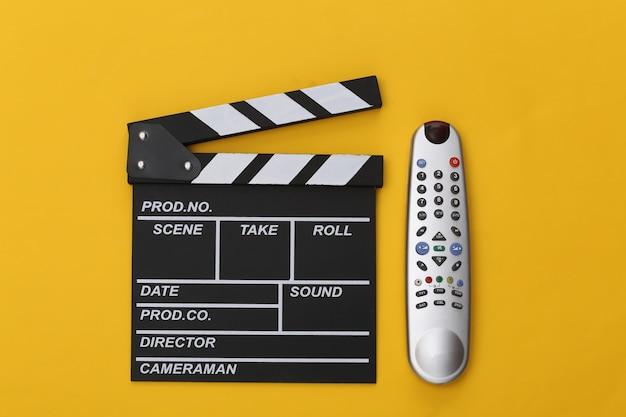 Доска с хлопушкой фильма и пульт от телевизора на желтом фоне. вид сверху