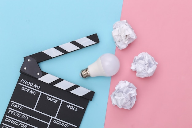Film clapper board and crumpled paper balls, light bulb on pink blue background. cinema industry, entertainment. top view