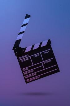Доска с хлопушкой пленки в синем красном неоновом свете. киноиндустрия, развлечения. минимализм, концепт-арт. 3d фото