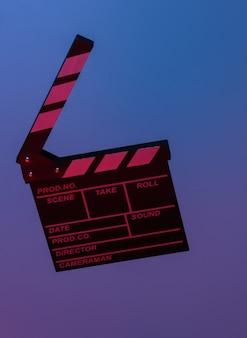 Доска с хлопушкой пленки в синем красном неоновом свете. киноиндустрия, развлечения. минимализм, концепт-арт